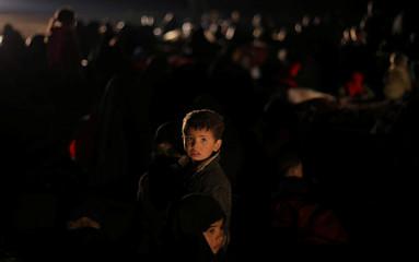 A boy looks at the camera, near the village of Baghouz, Deir Al Zor province
