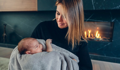 Mother hugging her baby in front of fireplace