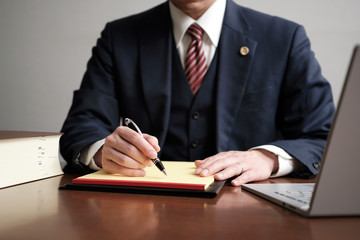 Obraz リーガルパッドにメモをする男性弁護士 - fototapety do salonu