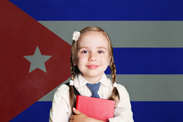 Cuba concept with happy child girl student with book against the flag of Cuban background