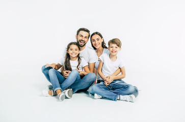 Relationship concept. Beautiful and happy smiling young family in white T-shirts are hugging and have a fun time together while sitting on the floor and looking on camera.