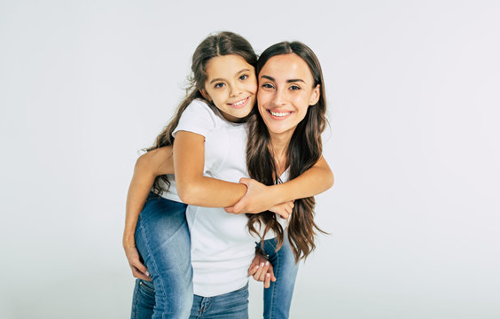 Beautiful young brunette mother holds on back her cute little daughter in white T-shirts isolated in studio