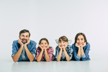 Close up photo of smiling beautiful modern family lying on the floor and looking on camera