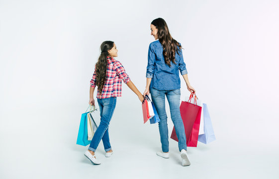 Beautiful mother and cute daughter in casual clothes with shopping bags in hands make purchases at the mall isolated on white