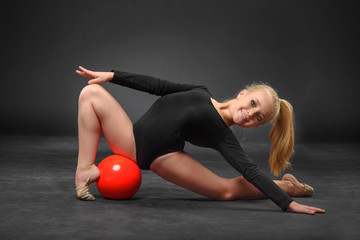 Young beautiful white caucasian girl gymnast doing gymnastic exercise with a red sports ball on black background