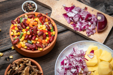 Mixture of vegetables, dried boletus mushrooms, sliced potato, red onion sliced and whole on a cutting board and spices, on old rustic wooden table.