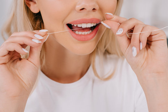 cropped view of woman flossing teeth with dental floss