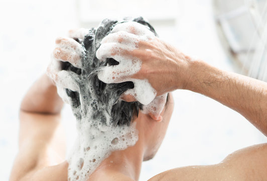 Closeup young man washing hair with with shampoo in the bathroom, health care concept