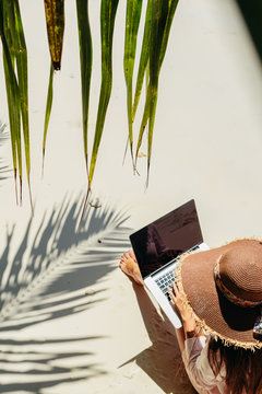 woman working remotely on laptop on beach in tropics