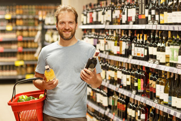 Customer standing in supermarket near shelves with alcoholic beverages and posing. Bearded man looking at camera and smiling. Client holding two bottles of wine and red basket.