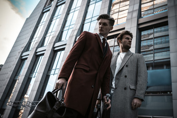 Two fashion men models posing on city street. Wearing in classic and casual closes. Suit, coat, shirt, sweater, boots and leather bag. Men model test near business center
