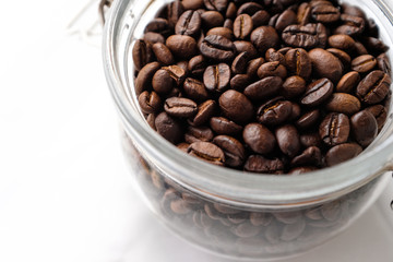 Wall Murals Coffee beans Close up dark roasted coffee beans in a glass jar on white cotton fabric background in natural light
