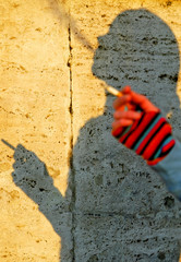 A woman casts a shadow as she smokes a cigarette in downtown Rome.