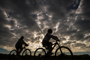 Couple of woman riding mountain bike in silhouette with great beautiful dramatic clouds sky in background - epic image for outdoor sport leisure activity