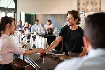 Bartender Serving Two Businesswomen Meeting For After Works Drinks
