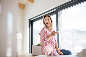 A young woman with smartphone moving in new home, sitting on table.