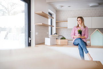 A young woman moving in new home, sitting on a counter in the kitchen.