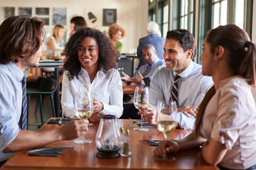 Business Colleagues Sitting Around Restaurant Table Drinking Wine Wall mural