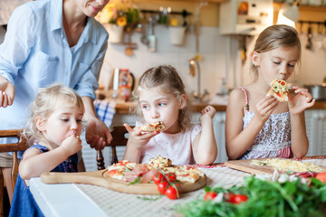 Children are eating and tasting italian homemade pizza cooking themselves together. Cute kids are enjoying delicious food in cozy home kitchen. Three girls at family dinner table. Lifestyle moment.