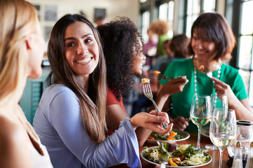 Group Of Female Friends Enjoying Meal In Restaurant Together