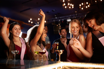 Group Of Dancing Female Friends Celebrating With Bride On Hen Party In Bar