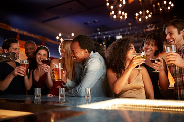 Group Of Couples With Friends Drinking In Bar Together