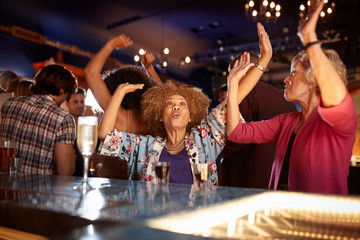Female Senior Friends Dancing In Bar Together