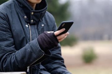 冬の屋外で指なし手袋でスマホを操作する男性