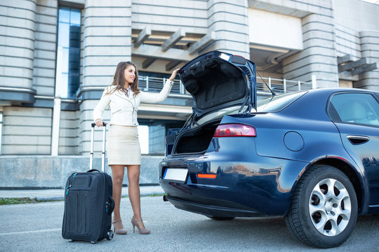 Fancy dressed young woman closing the trunk of the vehicle