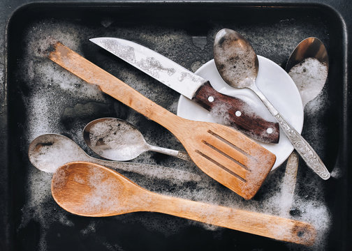 A white plate, a knife, wooden kitchen spatulas and spoons in the detergent foam on a black oven-tray. Washing dishes concept. Top view.