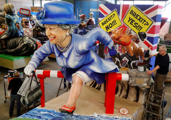A paper mache figure depicting Queen Elizabeth running for asylum towards the EU is seen during the presentation of the floats for the upcoming Rose Monday parade in Mainz