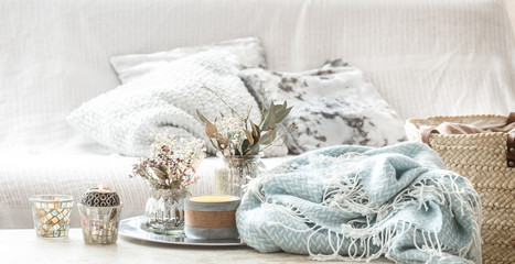 Home decorations in the interior. A turquoise blanket and wicker basket with a vase of flowers and candles