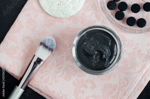 DIY activated charcoal face mask in a small glass bowl. Homemade cosmetics. Top view