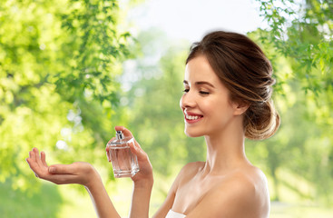 perfumery, beauty and luxury concept - happy smiling young woman spraying perfume to her wrist over green natural background