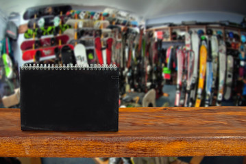 Mockup. Image of sport store with equipment for skiing. Defocused, blurred image. In the foreground is the top of a wooden table, counter.