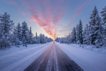 Road leading towards colorful sunrise at winter in Finland