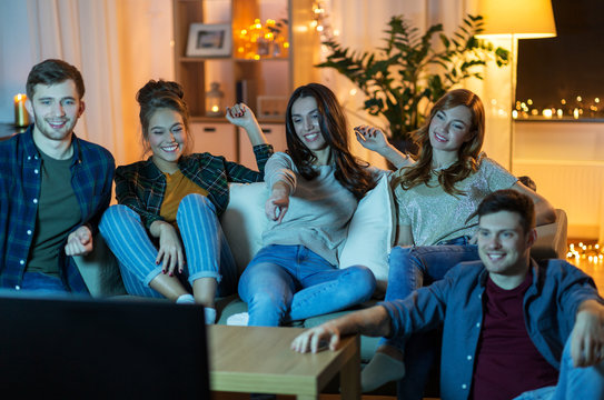 friendship, leisure, people and entertainment concept - happy friends watching tv at home in evening