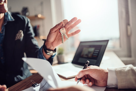 Client signing contract while real estate agent holding keys