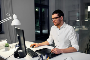 business, graphic design and technology concept - designer or businessman in glasses with computer and pen tablet working at dark night office