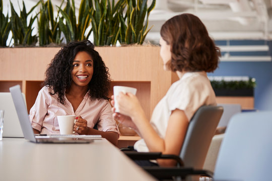 Two Businesswomen Working At Table In Modern Open Plan Office Drinking Coffee Together