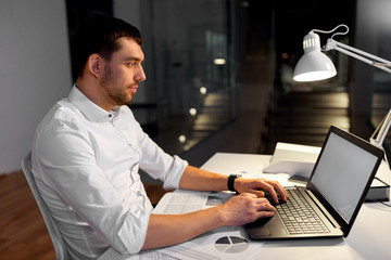 business, deadline and people concept - smiling businessman with laptop computer and papers working at night office