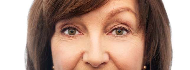 beauty, vision and old people concept - half of face of senior woman