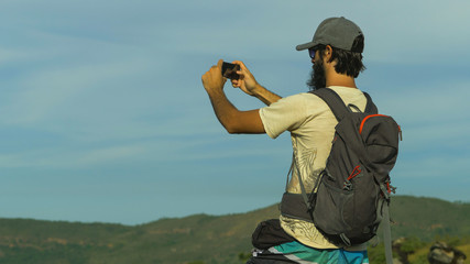 Tourist walking in nature photographing with smartphone