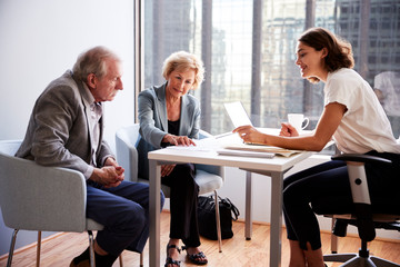 Senior Couple Meeting With Female Financial Advisor In Office