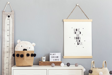 Stylish and cute scandinavian decor of  child room with mock up poster, white shelf, natural toys, hanging kid measure  basket for accessories and teddy bears. Minimalistic concept of interior.