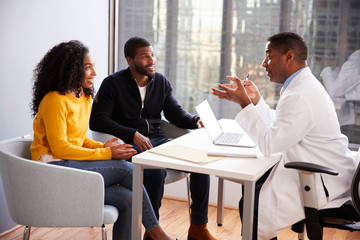 Smiling Couple Having Consultation With Male Doctor In Hospital Office