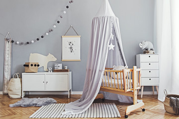 Stylish and cute scandinavian decor of  newborn baby room  with mock up poster , white design furnitures, natural toys, hanging grey canopy with wooden cradle, pillows, accessories and teddy bears.