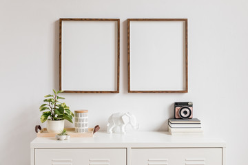 Minimalistic home decor of interior with two brown wooden mock up photo frames on the white shelf with books, beautiful plant in stylish pot, instant camera, elephant figure and home accessories.