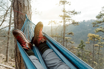 Man relaxing lying in hammock on top of mountain.