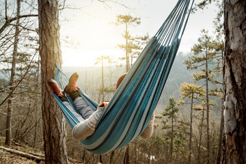 Young happy man relaxing lying in hammock on top of mountain. Wall mural